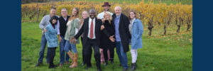 wine tour group with ron wamala in front of wine grapes